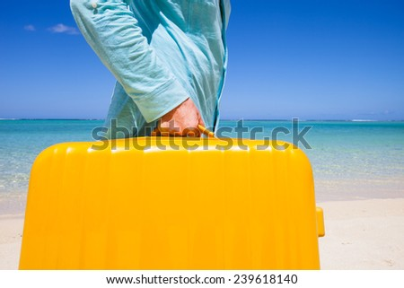travel background with a person carrying a yellow suitcase at a white sandy beach with a turquoise sea and a blue sky, concept for vacation holidays and arrival - stock photo