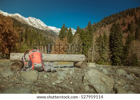 Travel backpack and shoes on a background of mountains