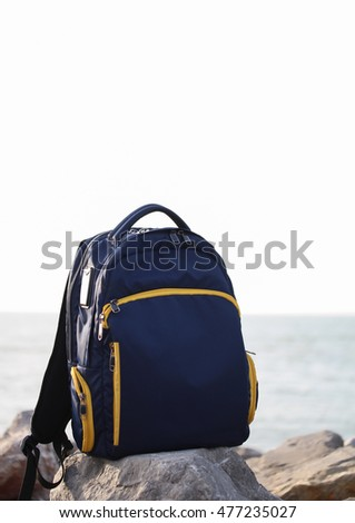 Travel backpack on the rocks by the sea.