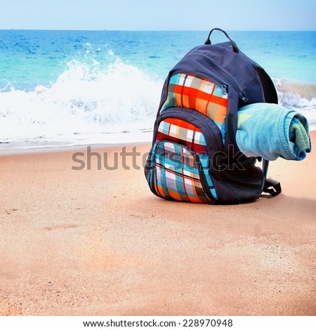 Travel Backpack with Towel on Summer Sea Beach. Holiday and Vacation Symbol - stock photo