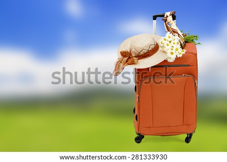 Travel bag with a straw hat and a bouquet of daisies on abstract nature background - stock photo