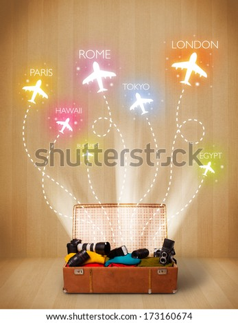 Travel bag with clothes and colorful planes flying out on grungy background - stock photo