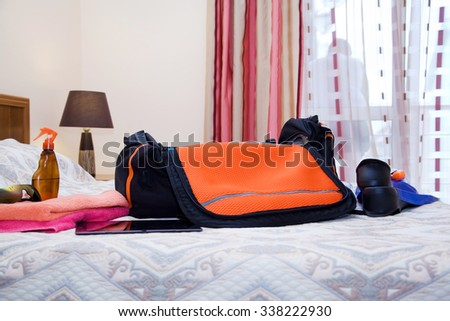 Travel bag with clothes in the hotel room - stock photo
