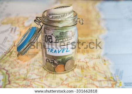 Travel budget - vacation money savings in a glass jar on world map. Collecting money for travel. Glass tin as moneybox with cash savings (banknotes and coins) on table and map as background.  - stock photo