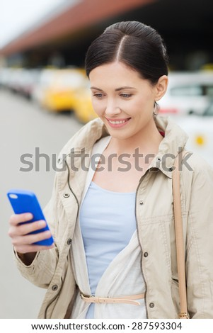 travel, business trip, people and tourism concept - smiling young woman with smartphone over taxi station or city street - stock photo