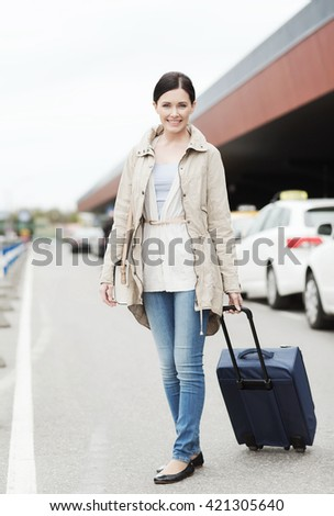 travel, business trip, people and tourism concept - smiling young woman with travel bag over taxi at airport terminal or railway station - stock photo