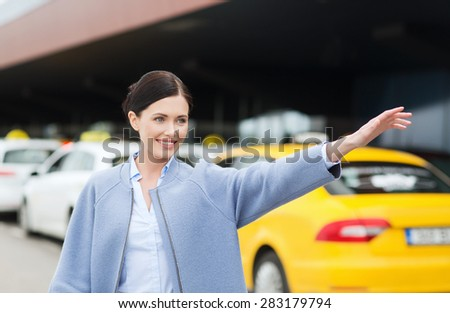 travel, business trip, people, gesture and tourism concept - smiling young woman waving hand and catching taxi at airport terminal or railway station - stock photo