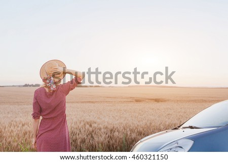travel by car, summer roadtrip, woman enjoying sunset in the fields near the road