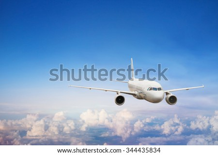 travel by plane, international flight, airplane flying in blue sky above the clouds - stock photo