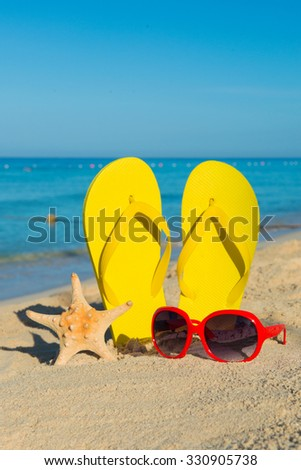Travel by sea. Beach vacation. Red sunglasses and yellow flip-flops on sandy seashore. - stock photo
