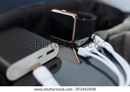 Travel charger and smart wrist watch and cable management for charge. This portable devices will let you stay connected to the network and work or have fun anywhere youn want.  - stock photo