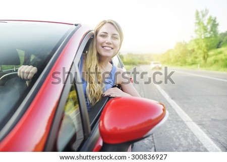 Travel concept. Attractive smiling girl in a red car. At sunset.