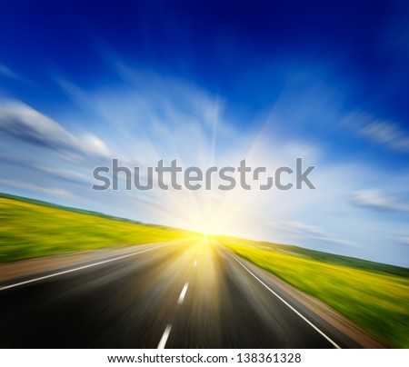 Travel concept background - motion blurred road in blooming spring meadow on sunset with blue sky