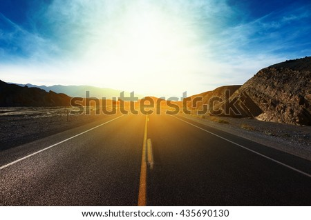 Travel concept background - road in blooming spring meadow on sunset. - stock photo