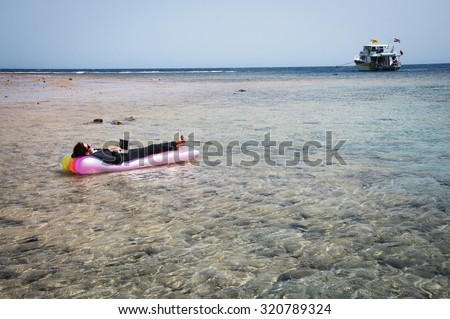 Travel concept â?? business woman working on floating mattress during summer holiday