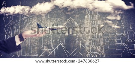 Travel concept, Businessman hand holding airplane, famous landmarks background