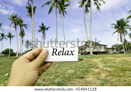 travel concept, cropped hand holding white canvas with word relax over blurred background of rural area.wooden house surrounded by coconut tree at sunny day and cloudy blue sky - stock photo