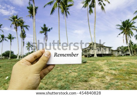 travel concept, cropped hand holding white canvas with word remember over blurred background of rural area.wooden house surrounded by coconut tree at sunny day and cloudy blue sky - stock photo