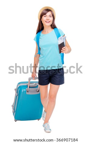 Travel concept. Full length studio portrait of pretty young woman holding passport with tickets walking with luggage. Isolated on white. - stock photo