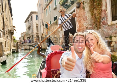 Travel concept - happy couple Venice gondola giving thumbs up hand sign excited looking at camera. Romantic young beautiful couple on vacation holidays sailing in venetian canal in gondole. Italy - stock photo