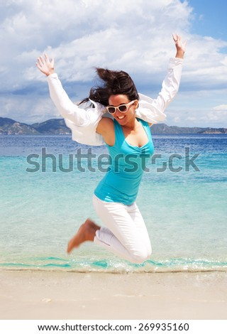 travel concept - happy girl jumping on the beach, summer holiday. - stock photo