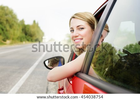 Travel concept. Happy smiling blonde woman in a red car at sunset.