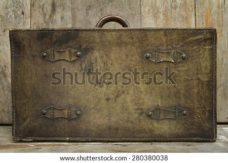 Travel concept on wood background with antique leather luggage - stock photo