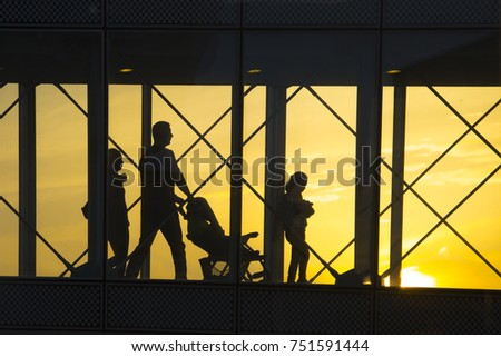 Travel concept, people in the airports ,Silhouette of family with luggage walking at airport,