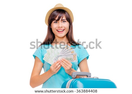 Travel concept. Portrait of smiling young woman with suticase holding money isolated on white background.