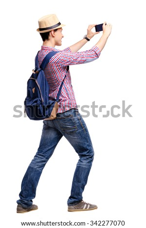 Travel concept. Studio portrait of handsome young man taking photo by his phone camera. Isolated on white. - stock photo