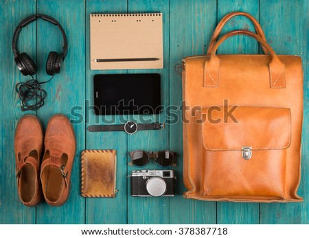 Travel concept - tablet pc, clothes, headphones, camera, shoes, watch and bag on the desk