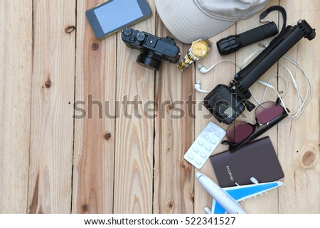 travel concept - top view of traveler's accessories and items with camera, medicine, sunglasses, hat, flashlight, watch, passport and on wooden background
