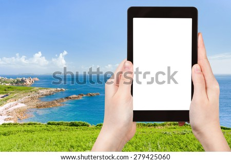 travel concept - tourist photograph panorama of Cote D Emeraude in Normandy, France on tablet pc with cut out screen with blank place for advertising logo - stock photo
