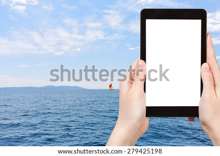 travel concept - tourist photograph red yacht in blue Adriatic sea, Dalmatia, Croatia on tablet pc with cut out screen with blank place for advertising logo - stock photo