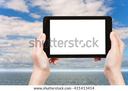 travel concept - tourist photographs North Sea in morning on tablet pc with cut out screen with blank place for advertising