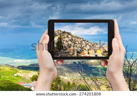 travel concept - tourist takes picture of Aidone town in Sicily in spring, Italy on tablet pc - stock photo