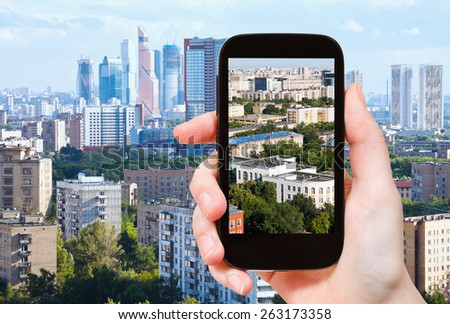 travel concept - tourist takes picture of Moscow City and urban living area in Moscow in summer afternoon on smartphone, - stock photo