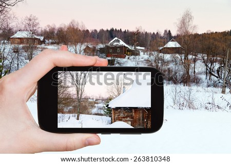 travel concept - tourist takes picture of rural landscape with snowy wooden houses in country at pink winter sunset on smartphone, Russia - stock photo