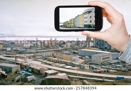 travel concept - tourist taking photo of Anadyr town skyline on mobile gadget in spring, Chukotka, Russia - stock photo