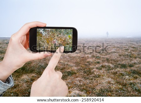 travel concept - tourist taking photo of Arctic tundra in spring, Siberia, Chukotka on mobile gadget Russia - stock photo