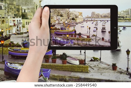 travel concept - tourist taking photo of boats in old urban port in valletta at sunset on mobile gadget, Malta - stock photo