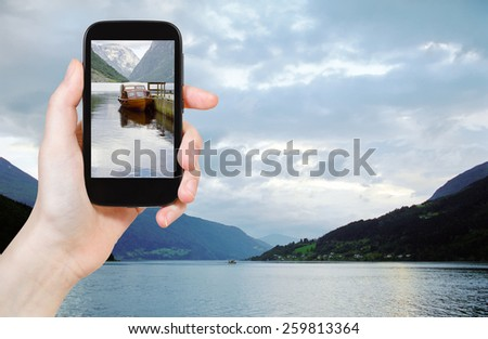 travel concept - tourist taking photo of fjord in Norway in evening on mobile gadget - stock photo