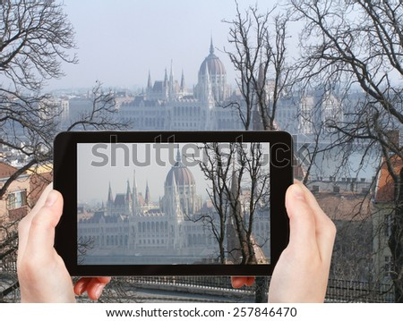 travel concept - tourist taking photo of Hungarian Parliament Building in spring morning on mobile gadget, Hungary - stock photo