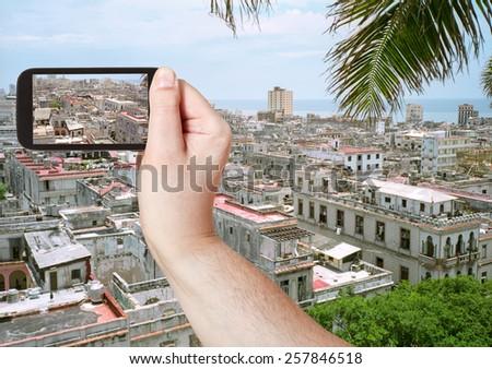 travel concept - tourist taking photo of old Havana city on mobile gadget, Cuba - stock photo