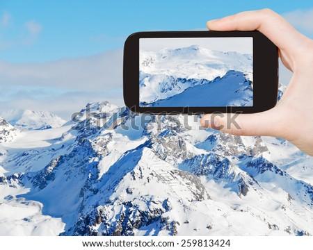 travel concept - tourist taking photo of snow mountains in Alpes Paradiski skiing domain, Les Coches - Montchavin , France on mobile gadget - stock photo