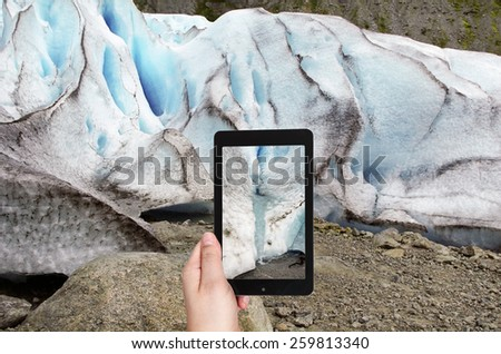 travel concept - tourist taking photo of spring in briksdal glacier in Norway on mobile gadget - stock photo