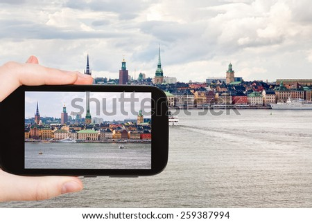travel concept - tourist taking photo panorama of Stockholm city in autumn day, Sweden on mobile gadget - stock photo