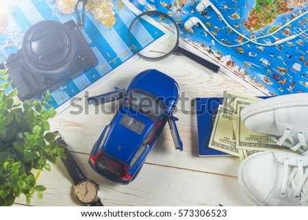 Travel - concept. Traveler's accessories, Essential vacation items, camera, touristic maps, on the white desk. Travel background. Car journey planning. Tourist essentials. Space for text