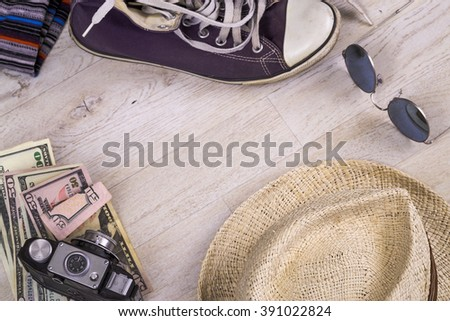 travel concept with hat, sunglasses, moneys, camera and shoes