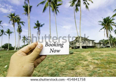 travel concept with word booking now over blurred background of rural area.wooden house surrounded by coconut tree at sunny day and cloudy blue sky - stock photo